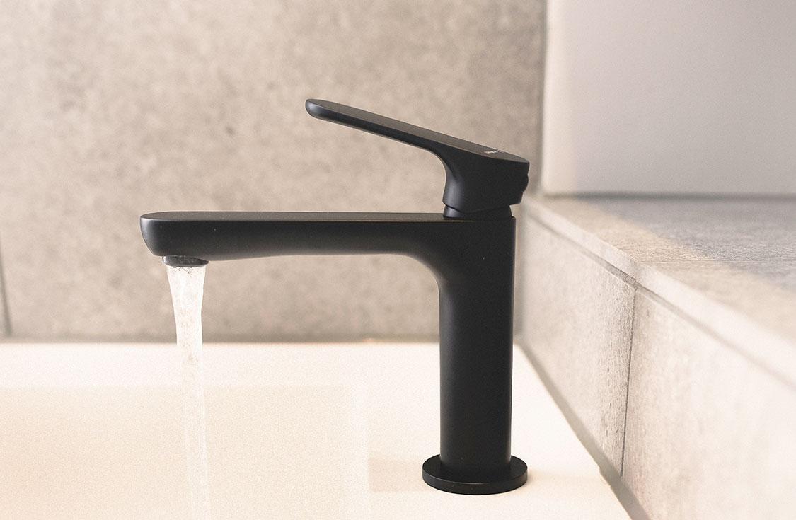 Viser den svarte kranen med rennende vann